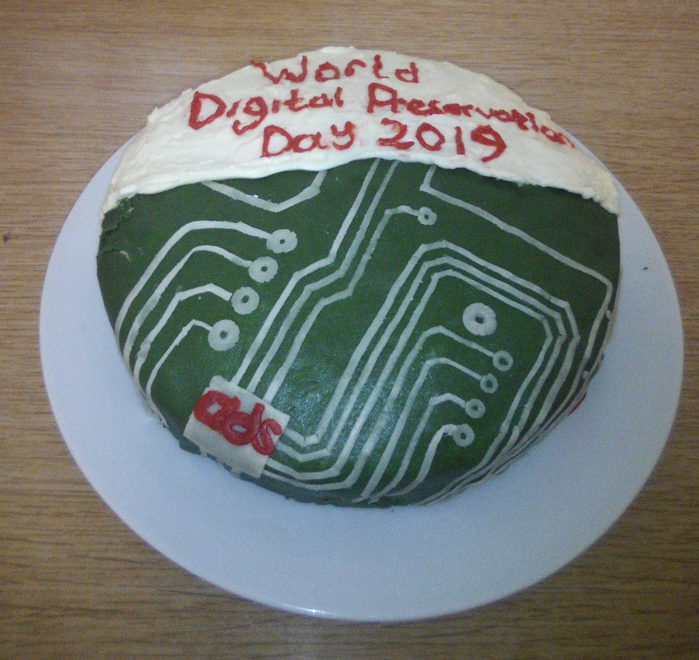 A cake with a green and white circuit board design and the text 'World Digital Preservation Day 2019'.