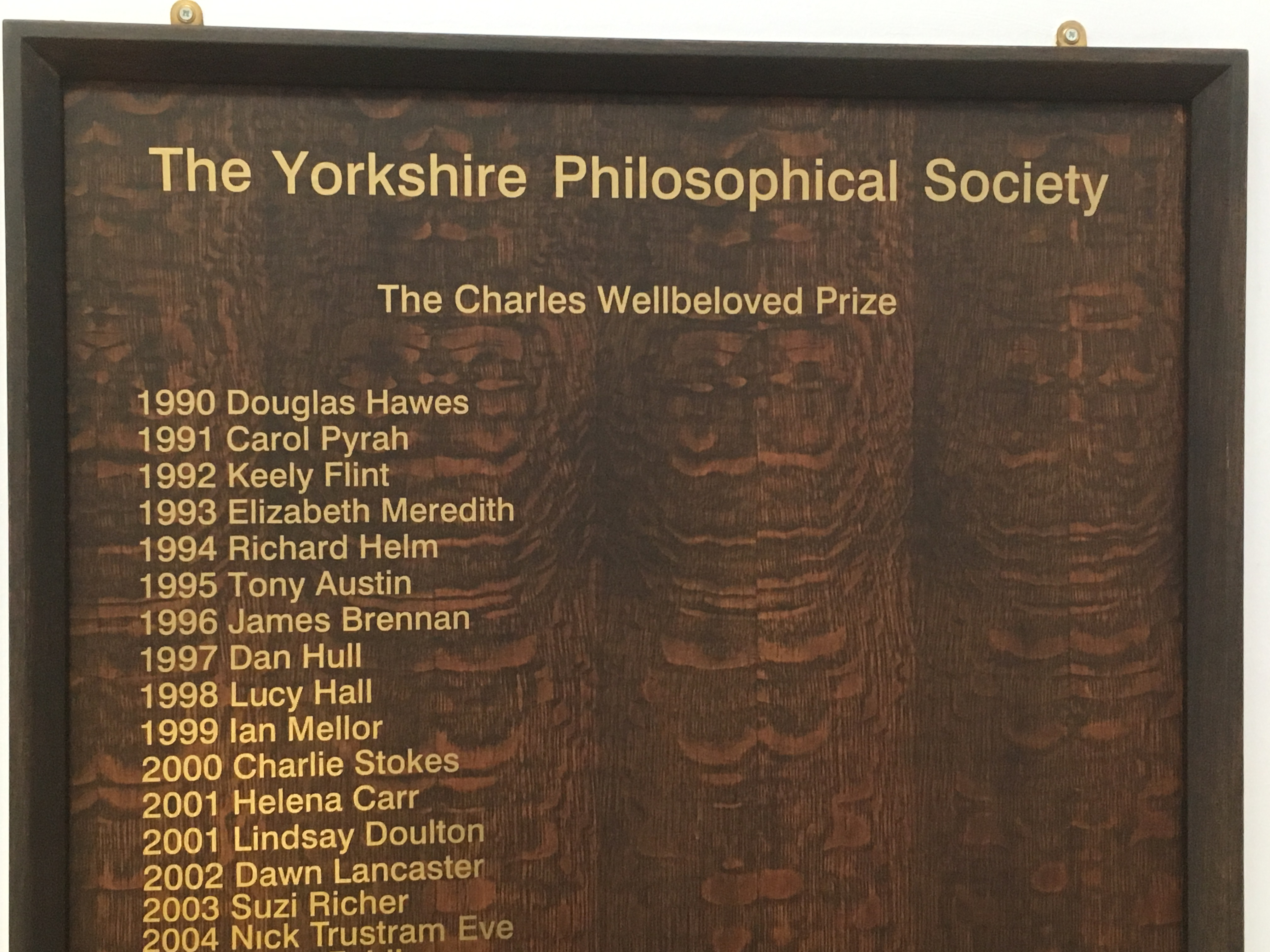 Photograph of the Charles Wellbeloved prize winners board located in the Archaeology Department. Tony's name is listed as prize winner for 1995.