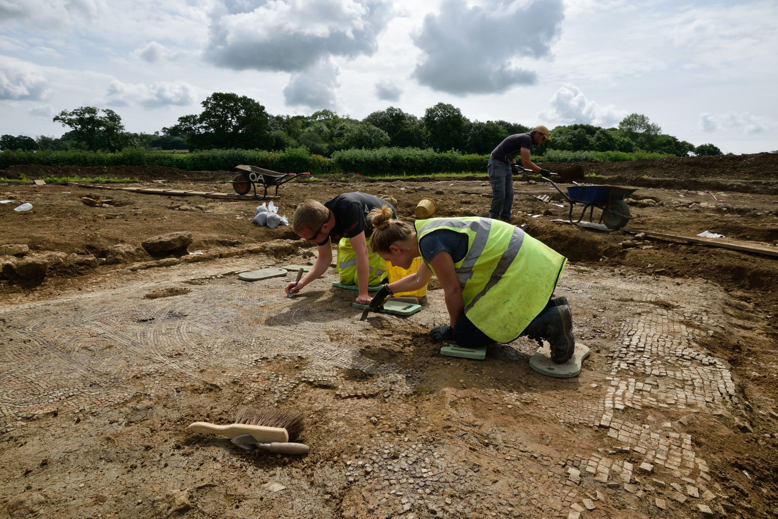 Photograph of two archaeologists on kneelers use their trowels to reveal a mosaic at a Roman villa.