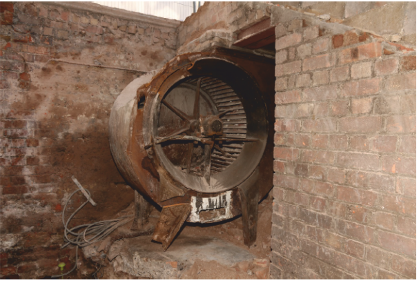 Plate 3 : Extractor fan for air ventilation located at the west end of no. 143 Borough High Streetat basement level below the stairs in the access tunnel, looking northwest (18 Mar 2015).